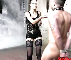 Caged bdsm sub gets cock tugged outdoors